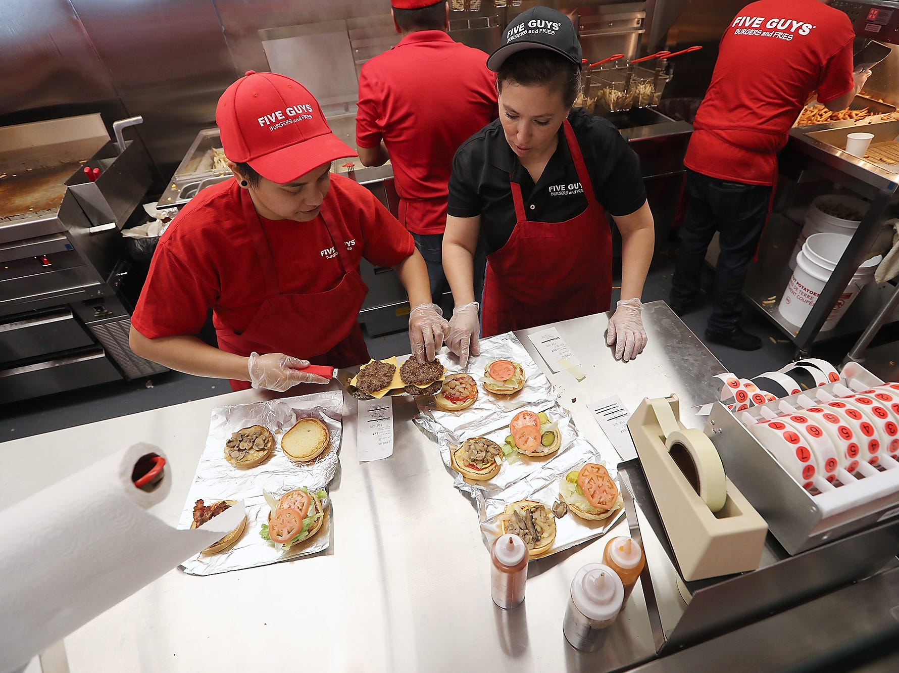 Louie Acoba (left) and General Manager Rebecca Hager assemble burgers at Five Guys Burgers and Fries in Silverdale on Monday, November 5, 2018.
