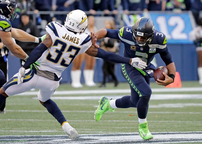 Seattle Seahawks quarterback Russell Wilson (3) scrambles away from Los Angeles Chargers' Derwin James.