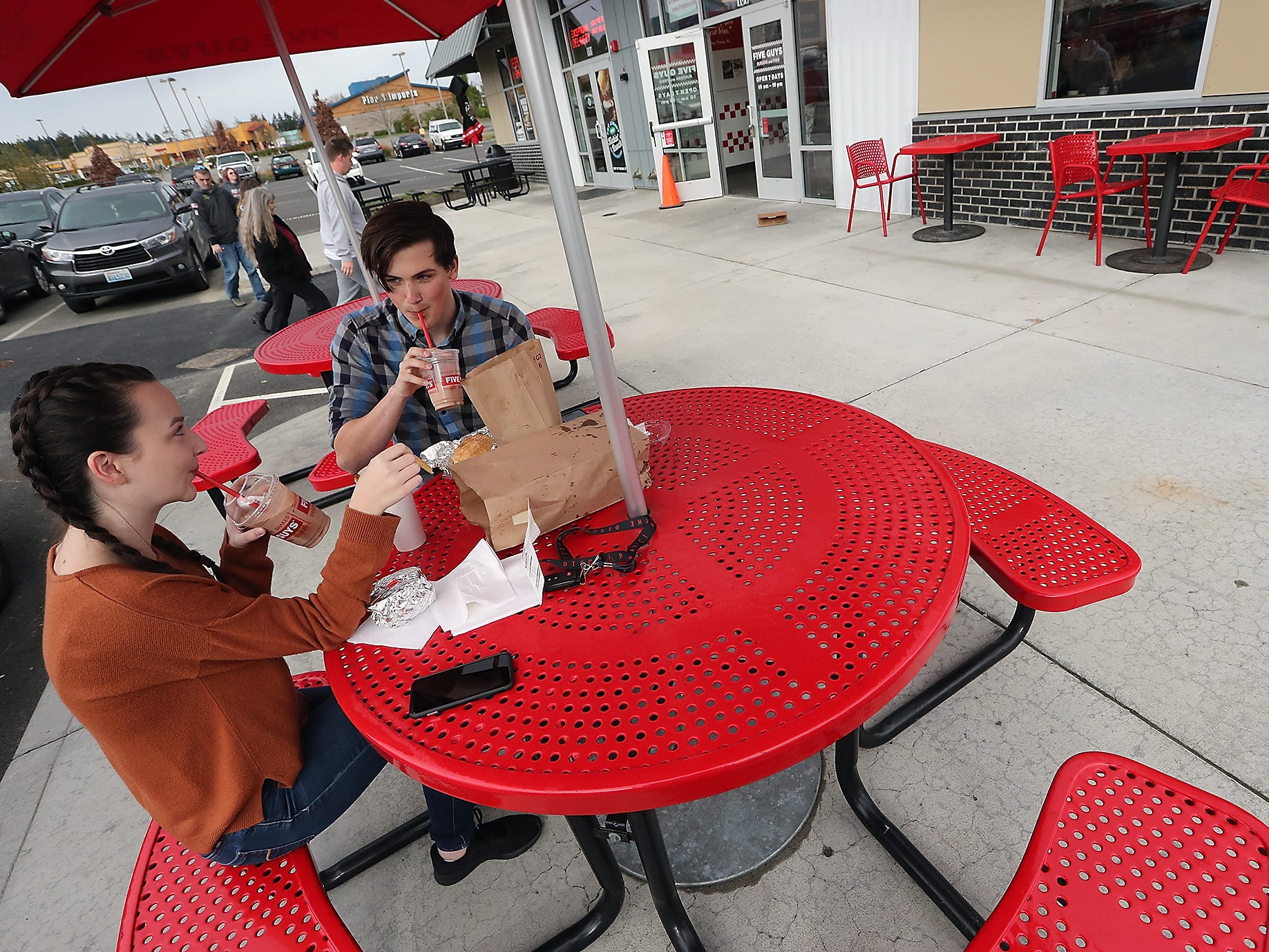 Nicole Lynch and  Mason Heaman sip their milkshakes as they enjoy their lunch outside at Five Guys Burgers and Fries in Silverdale on Monday, November 5, 2018.
