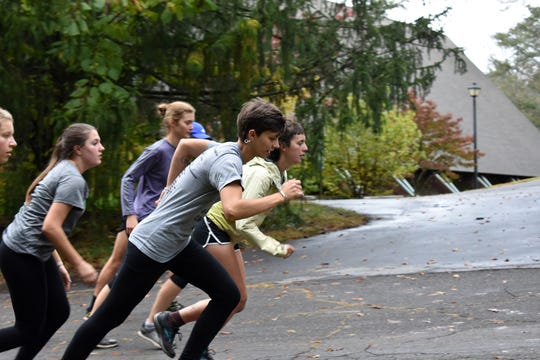 Sophie Willihnganz (left) and Ellie Goldstein lead a pack of runners in a recent workout at Warren Wilson.
