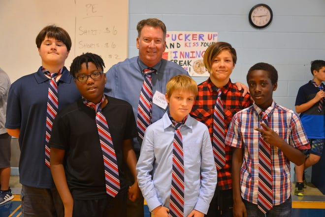 Glen Outlaw, center, recently visited Jackson Middle School in Titusville with Tied Together of the Space Coast.