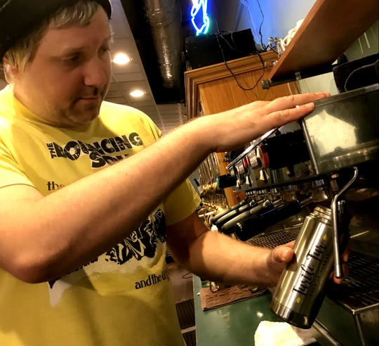 Michael Frank, a barrista at Uncommon Grounds Coffee and Tea in Burlington, flushes a customer's coffee mug with steaming water on Monday, Nov. 5, 2018.
