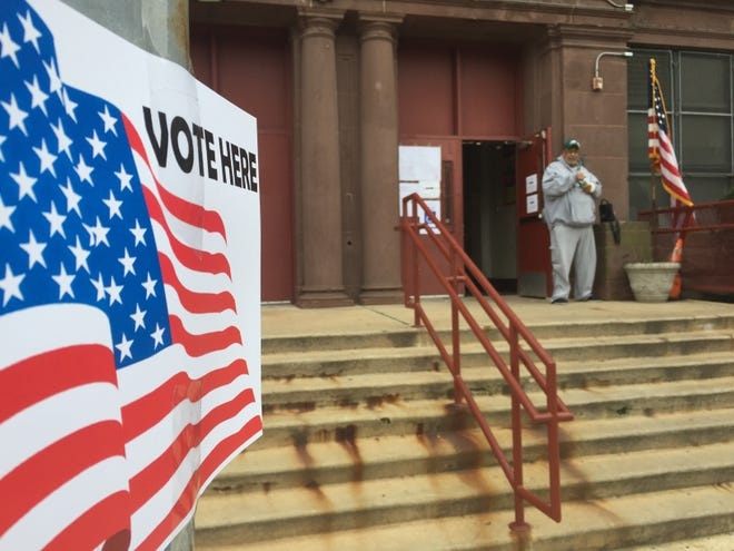 A Camden man stands outside a polling place at Cramer Elementary School in November 2017. City voters will vote Tuesday on how to fill school board seats.