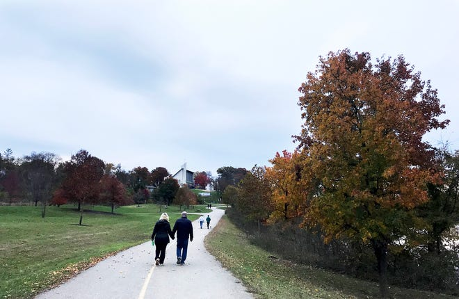 A couple takes a walk at Winton Woods Park Sunday, November 4, 2018.