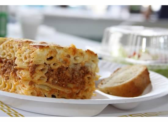 Pastitsio, one of the menu items, a hearty baked macaroni and beef casserole, topped with béchamel sauce, and served with bread and side salad.