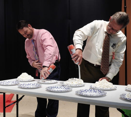 Assistant Principals Tony Meiser and John Casey load up paper plates with whipped cream for students to smash into the faces of selected teachers at Coshocton Elementary School.