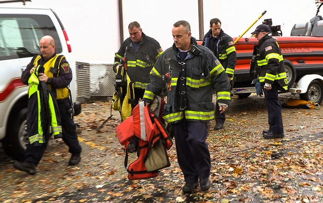 In this Sunday, Nov. 4, 2018, photo, Skokie and Lake Forest Fire emergency personnel move toward the Lake Front at Highland, Park, Ill. Authorities say a 46-year-old man has died and a 52-year-old woman is missing after going swimming in hazardous waters in Lake Michigan near the Chicago suburb.