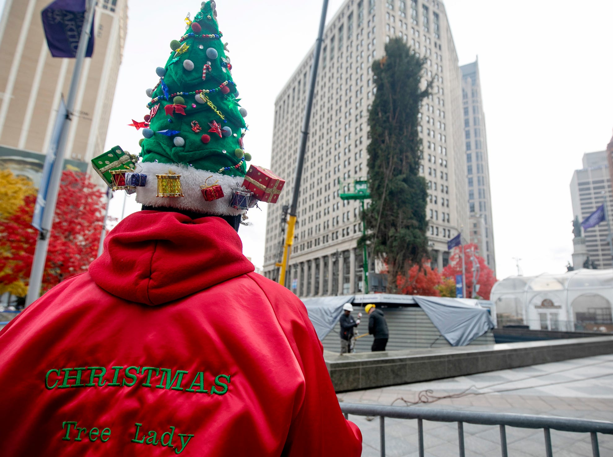 "DTE retiree Amelia Sharpe, of Detroit, dons her homemade Christmas hat as workers take on a 60-foot-tall Norway spruce as they place it in Campus Martius on Monday, Nov. 5, 2018. ""I haven't missed this in 15-years"" said Sharp."