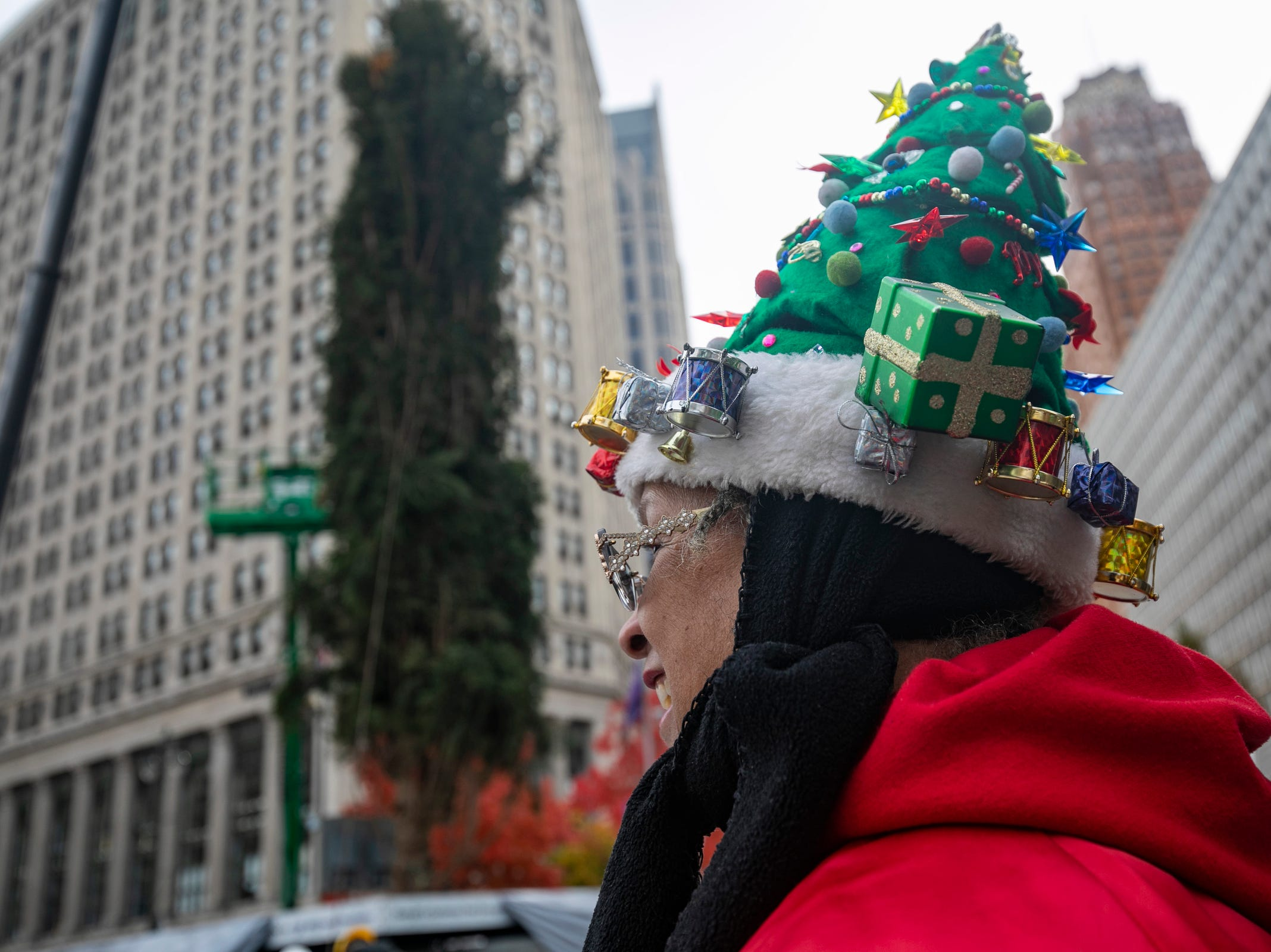 DTE retiree Amelia Sharpe, of Detroit, dons her homemade Christmas hat as workers install a 60-foot-tall Norway spruce in Campus Martius on Monday, Nov. 5, 2018.