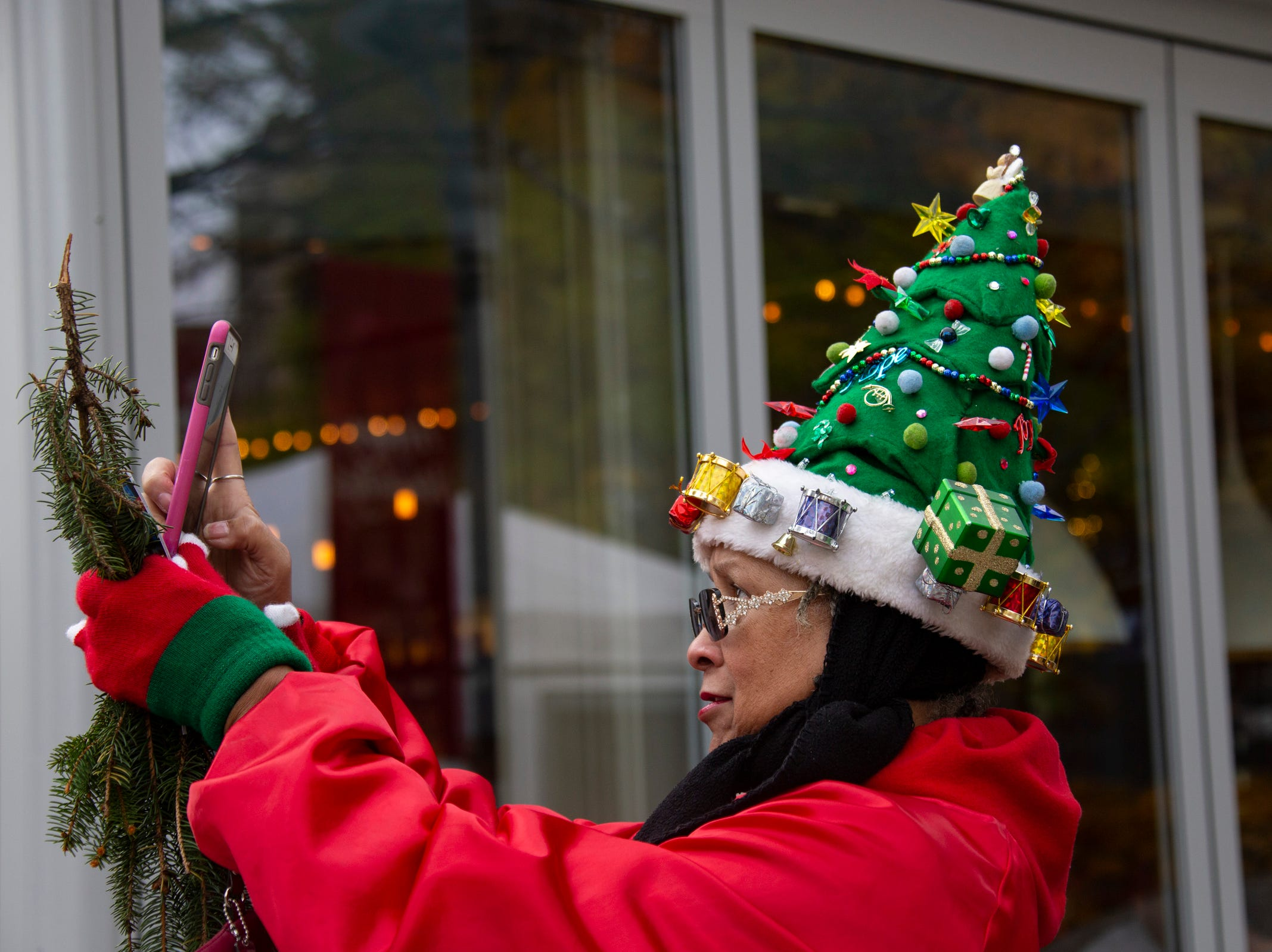 "DTE retiree Amelia Sharpe, of Detroit, dons her homemade Christmas hat as workers install a 60-foot-tall Norway spruce in Campus Martius on Monday, Nov. 5, 2018. ""I haven't missed this in 15-years,"" said Sharp. The Downtown Detroit Partnership and DTE Energy Foundation present the 2018 Detroit tree lighting and light up Beacon Park lineup for November 16 ceremonies."