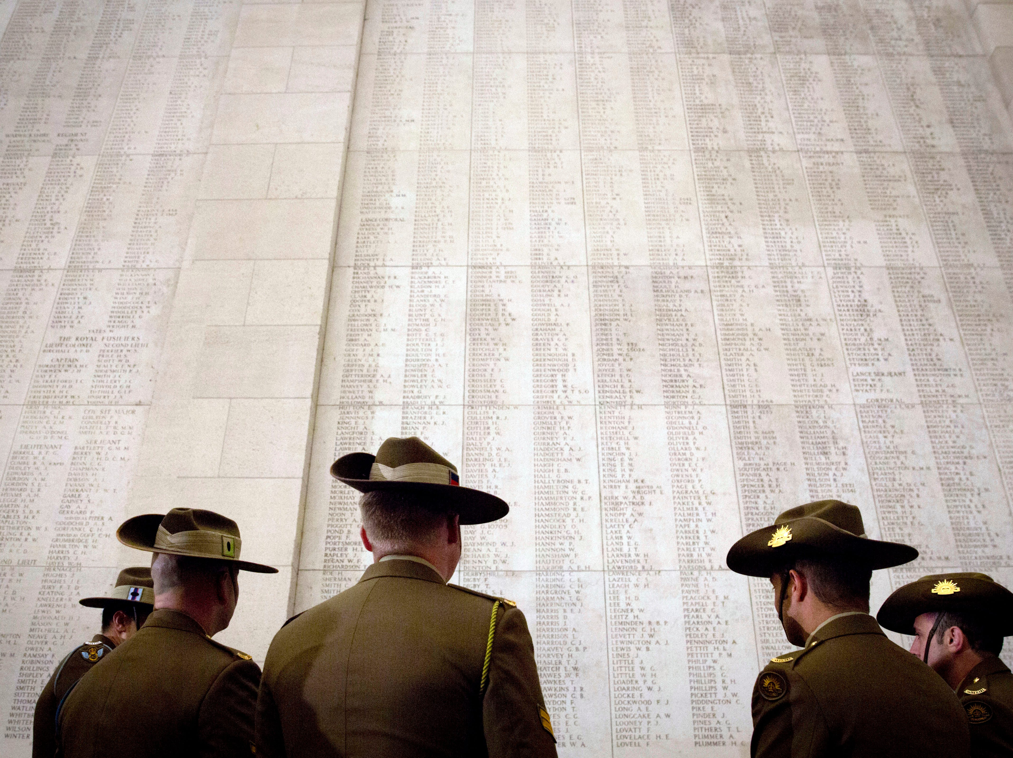 Australian soldiers look up at the names of World War I missing engraved on the Menin Gate in Ypres, Belgium, Monday, Nov. 5, 2018.