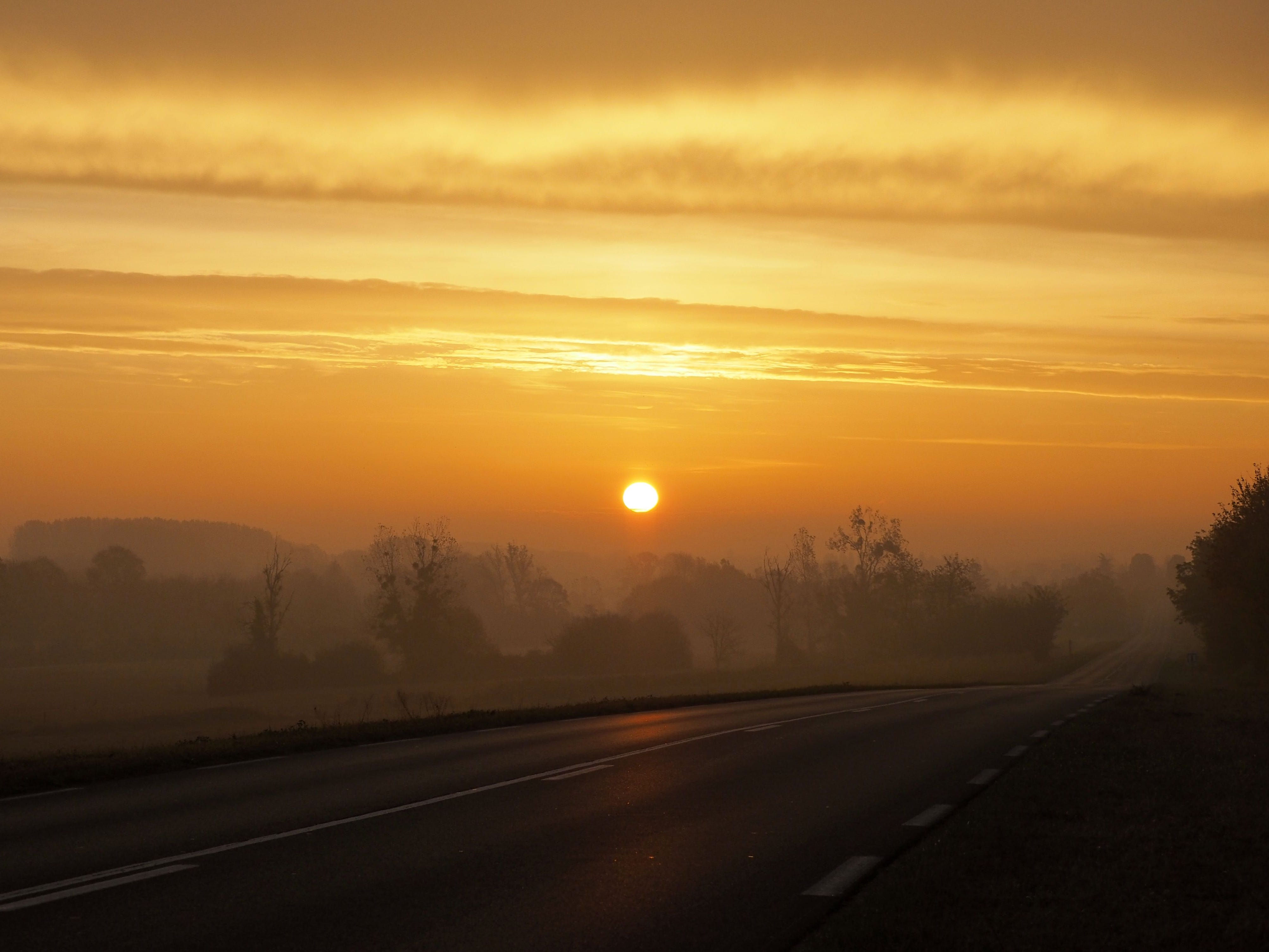 The sun rises over fields along a road near Chateauroux, central France, on Nov. 4, 2018.