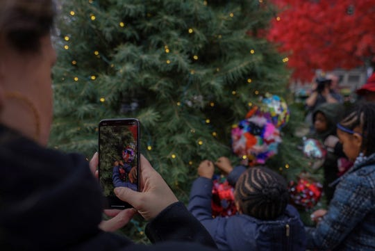 Children help decorate a tree near Campus Martius park while an adult watches.