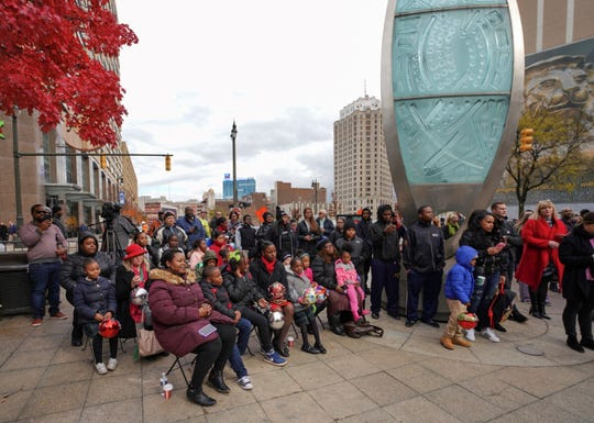 a crowd gathers at campus martius to watch the christmas tree being raised on monday