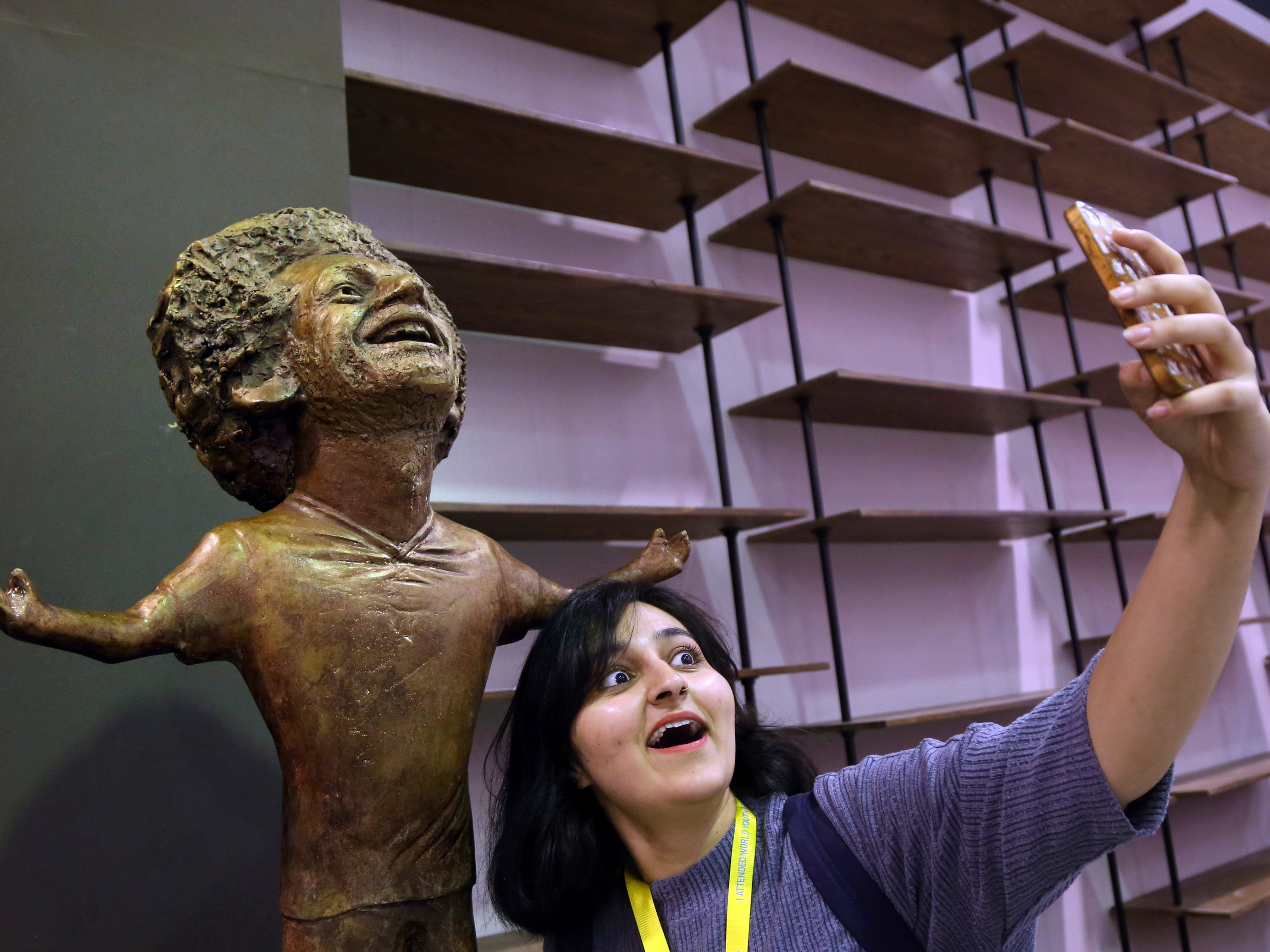 A participant at an international youths gathering poses for a selfie with a bronze statue of Liverpool striker Mohammed Salah in Sharm El Sheikh, Egypt, Monday, Nov. 5, 2018.