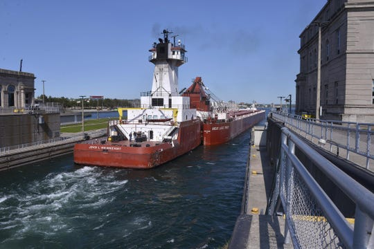 In this file photo, the Great Lakes Trader and the tug Joyce L. VanEnkevort exits the Poe Lock at the Soo Locks in Sault Ste. Marie.