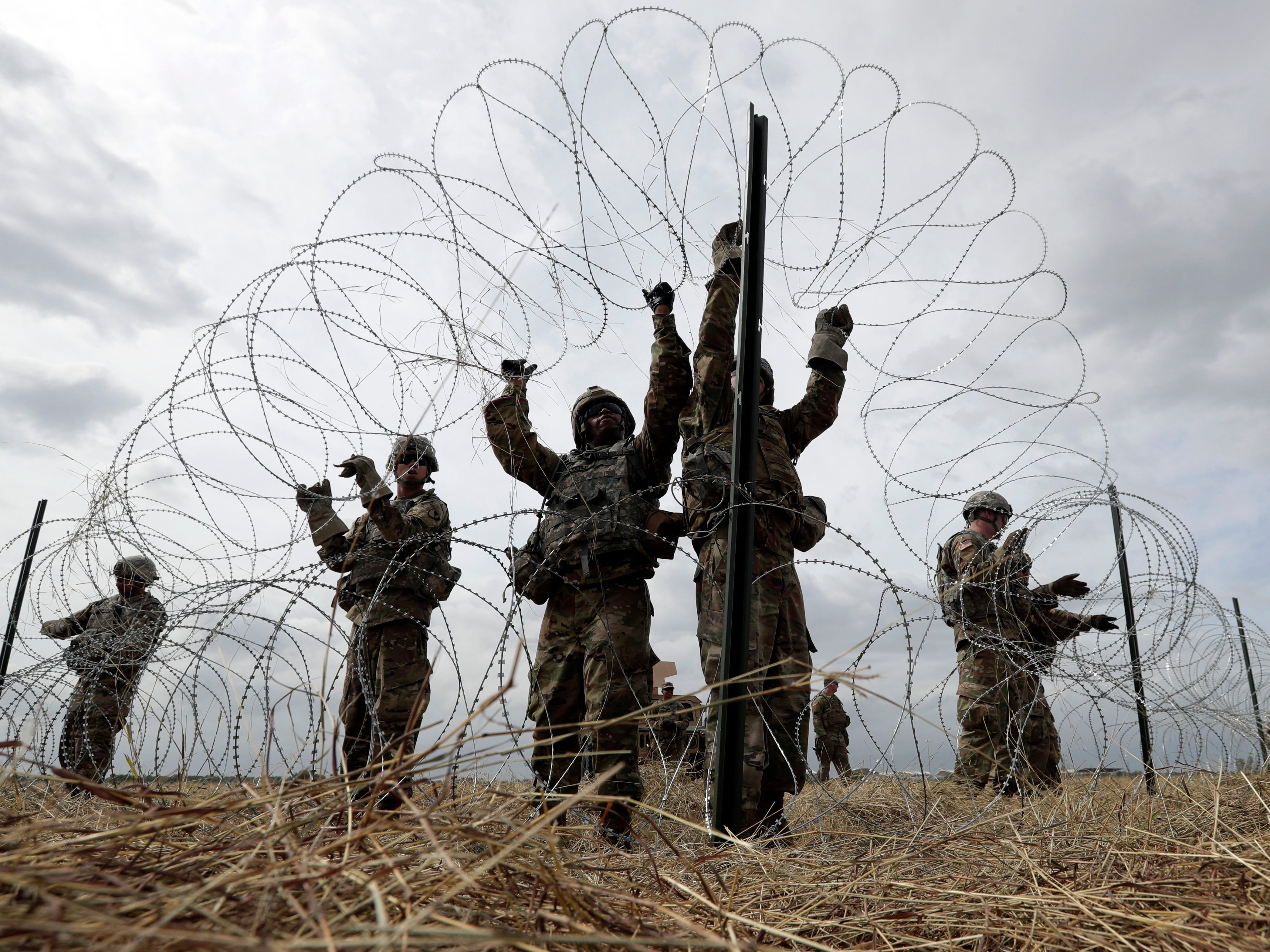 Members of a U.S Army engineering brigade place Concertina wire around an encampment for troops, Department of Defense and U.S. Customs and Border Protection near the U.S.-Mexico International bridge, Sunday, Nov. 4, 2018, in Donna, Texas.