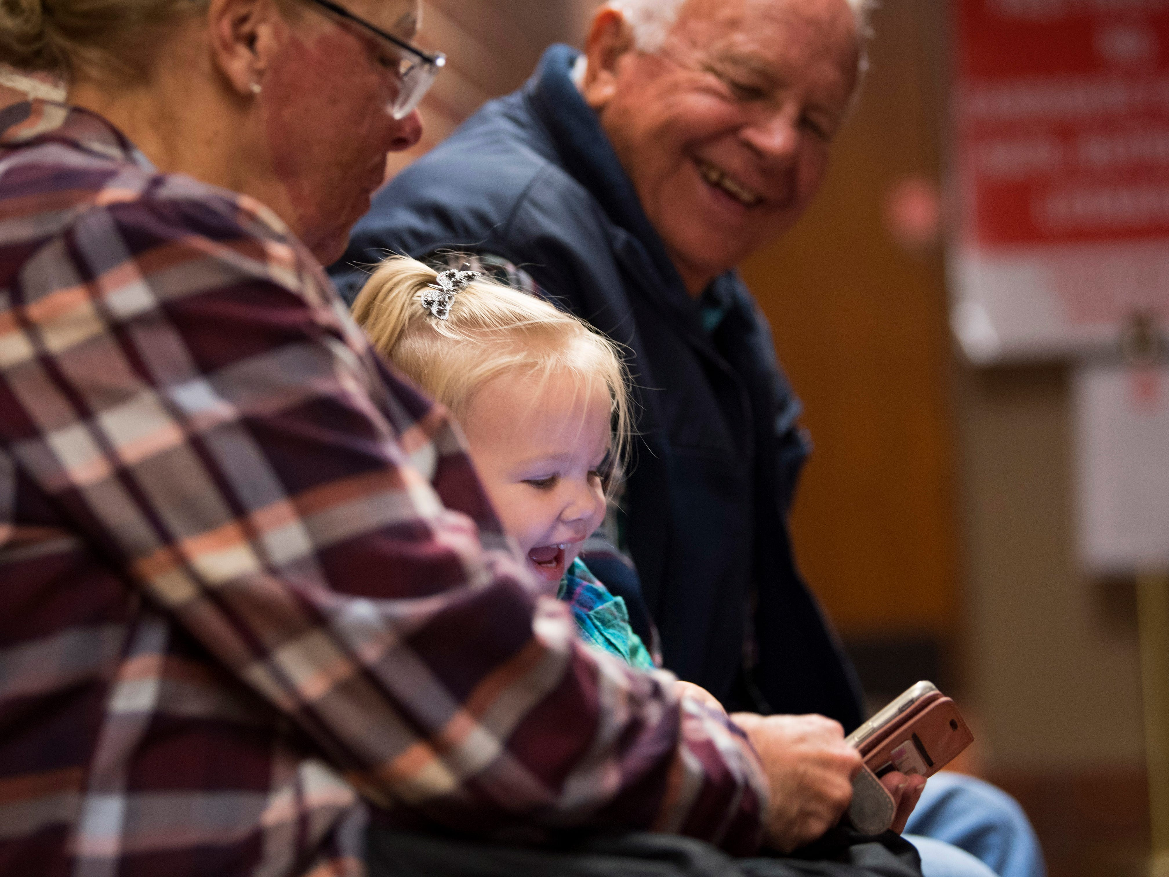 """Ella Lomax, 2, stays entertained by watching kid videos with her grandmother, Cindy Reich, left, and great grandfather Charles Riley at the Vanderburgh County Civic Center Monday. The adults were waiting to get their early votes in while Ella was happy to sing along with """"Baby Shark"""" and the """"Gummy Bear Show."""""""