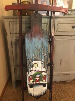 Each family member part of Rusted Roots has their own technique to designing a sled. This one features a snow-covered vintage red pickup truck with a wreath adorning its front.