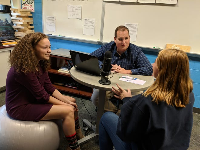 Port Clinton High School juniors Alanna Read, left, and Allison Dickman, right, record an episode of the PCHS Creative Writing Class podcast with teacher, Mr. Joe Miller.