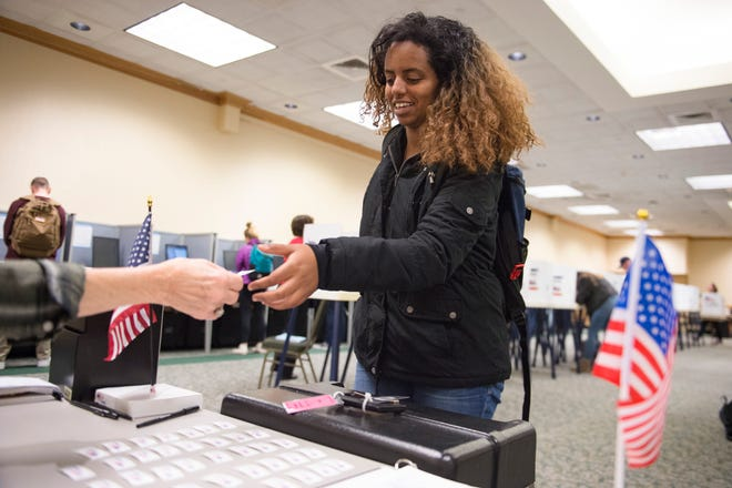 Nardos Habteyonas receives a sticker after dropping her ballot in a drop box during early voting at CSU's Lory Student Center on Monday, November 5, 2018. Election judges said a steady stream of students were turning out to vote the day before Election Day.