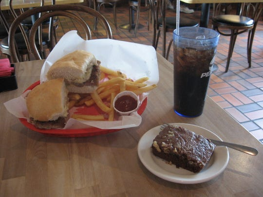 This file photo shows a lunch at Deli Works featuring the Braterly Love sandwich (bratwurst sliced in two halves, smothered with sauerkraut, Swiss cheese and hot mustard) with French fries, a fountain drink and a brownie.