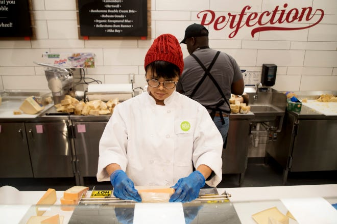 Assistant team leaders Liza Starman and Elton Williams prepare the cheese department at the new Fort Myers Whole Foods Market that is opening on Wednesday, Nov. 7.