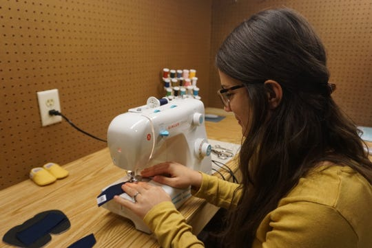 Grace Menocal of De Pere works on one of her baby booties for her company, jamBam! booties.