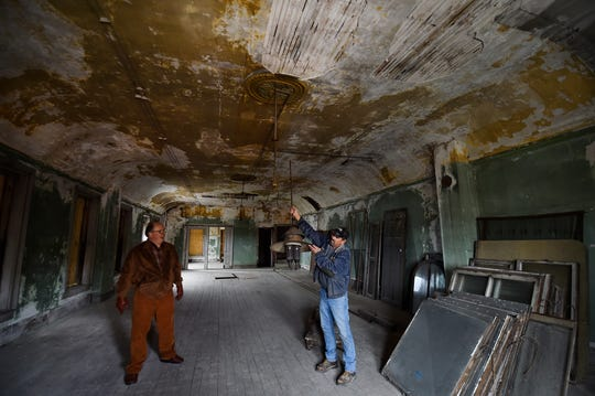 Tom Skubal, right, displays one of the gas chandeliers that lit Grimmer's Hall, a ballroom that occupied the top floor of the former Selner Plumbing & Heating building in Kewaunee. Skubal is working to gut the building for renovations by the building's new owner, Art Schiller, left.