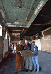Art Schiller, from left, Maynard Lufter and Tom Skubal show a tin ceiling tile in which 100-year-old Lufter's father Frank installed in the 1920s inside the former Selner Plumbing & Heating building in Kewaunee. The three-story building, now owned by Schiller, is being renovated with the help of historian Skubal.
