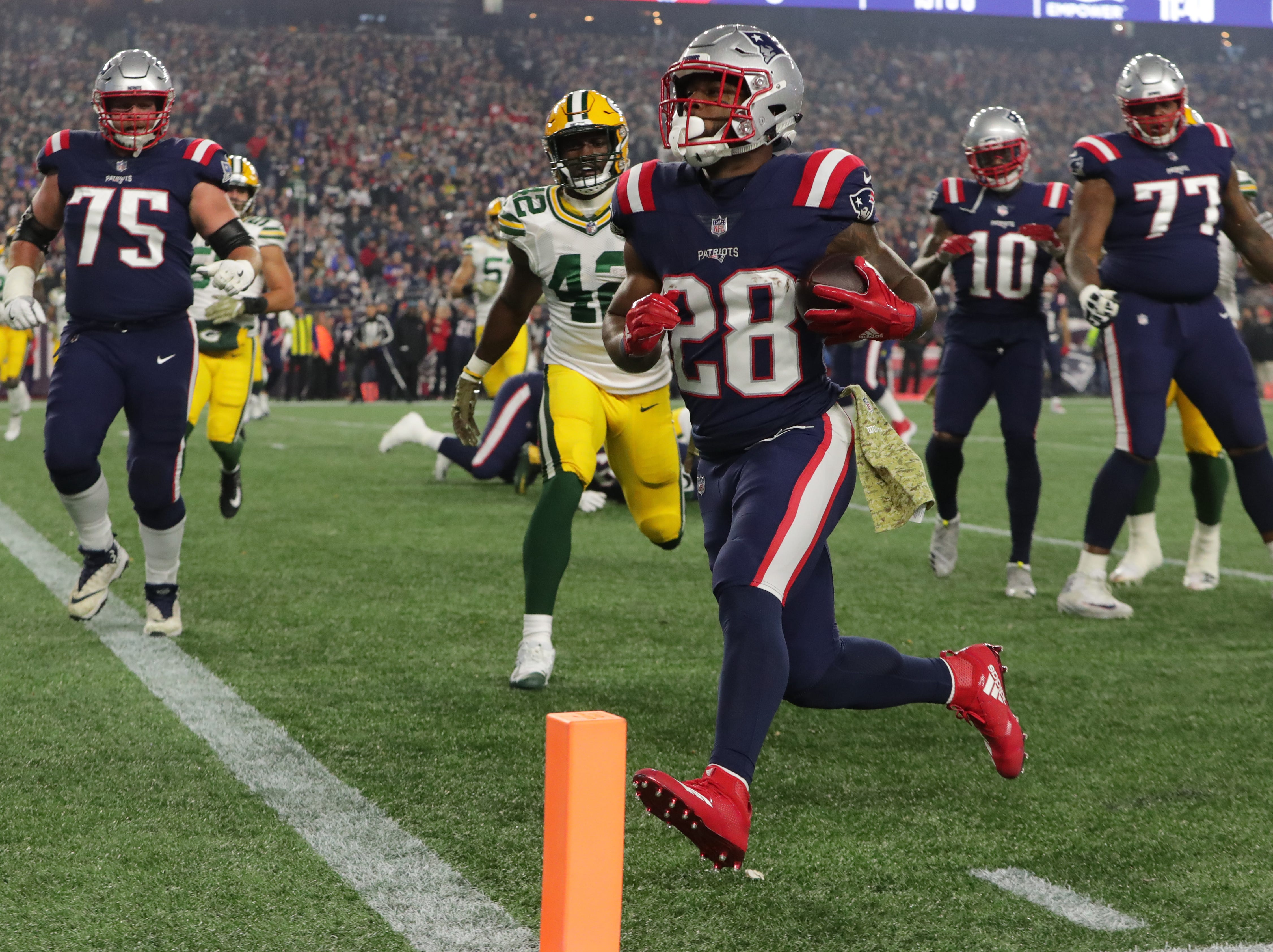 New England Patriots running back James White (28) runs eight yard for a touchdown during the first quarter of their game against the Green Bay Packers Sunday, November 4, 2018 at Gillette Stadium in Foxborough, Mass.
