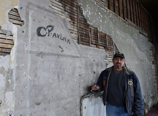 """Tom Skubal stands next to the """"C. Pavlick'' signature he discovered under the wall layers in the Selner Plumbing & Heating building. The autograph was likely made in the 1930s."""