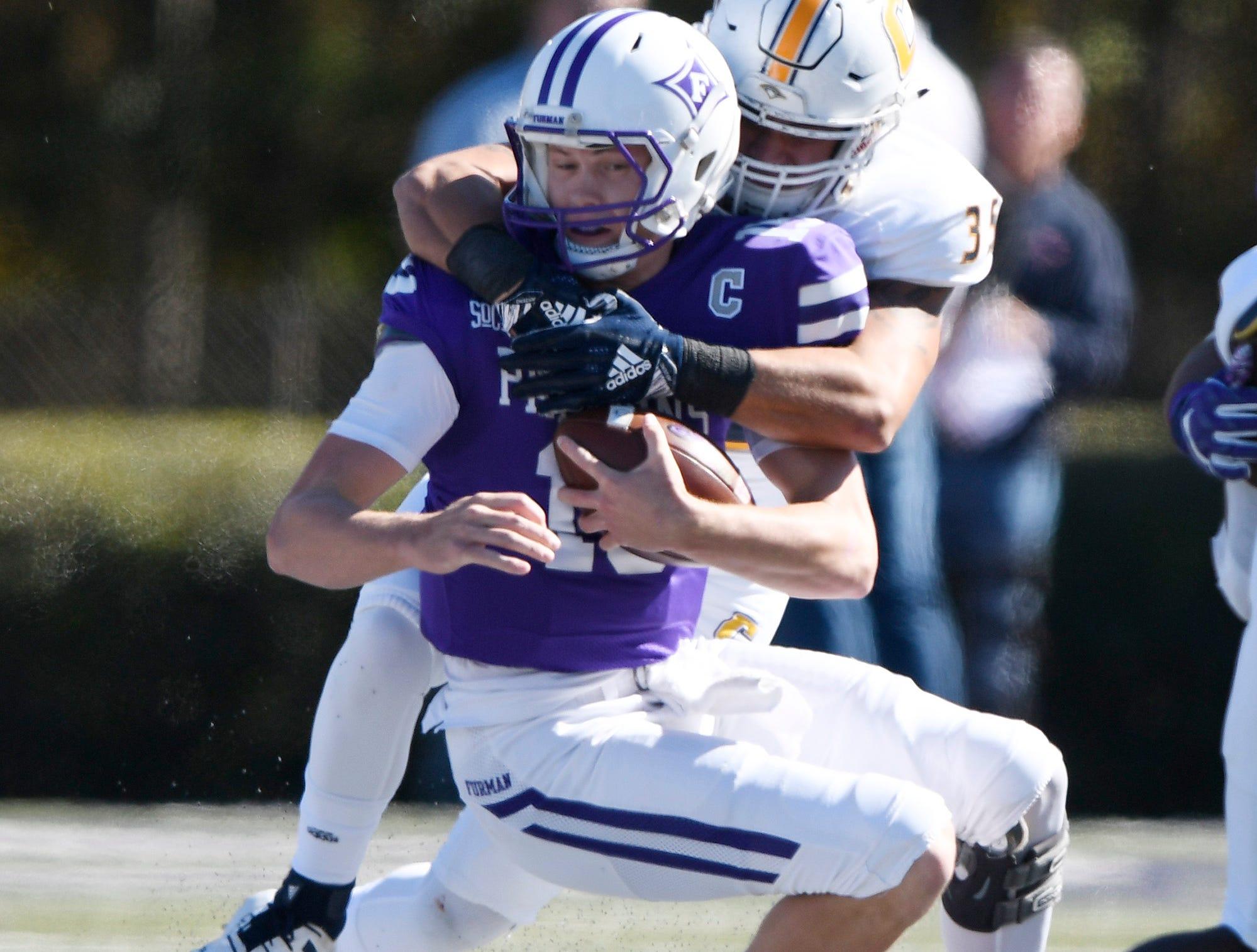 Furman quarterback Harris Roberts (15) is sacked by Chattanooga's Michael Bean (35) Saturday, November 3, 2018, at Paladin Stadium.