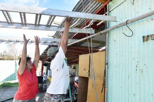 "May Valiente, 50, tries to help her husband, Rodel Valiente, 53, as he lifts a metal frame at their Tinian home on Nov. 3, 2018. The couple's home was heavily damaged by Super Typhoon Yutu. Rodel Valiente said he is using material that landed in his yard to make temporary repairs. ""As long as we survive,"" he said."