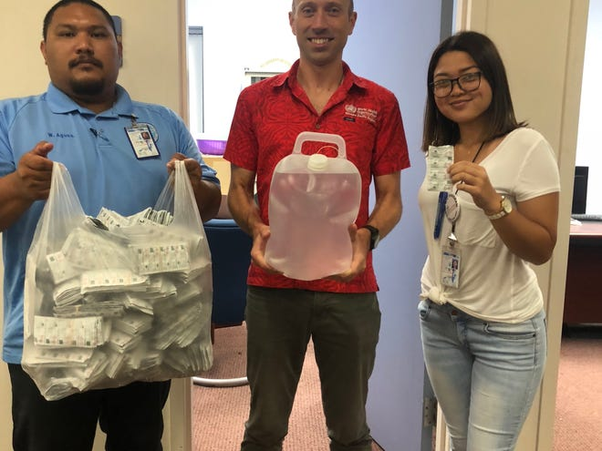 Wil Aguon, Sean Casey, and Robin Romero posing with water treatment supplies