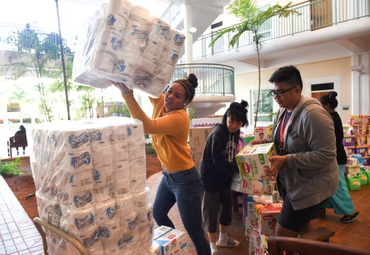 University of Guam Women and Gender Studies students Victoria Botelho, left, Esther Chun, center, and Jester Calalang stack Alee Shelter donations onto a cart at the UOG campus on Nov. 5, 2018. The students were able to get their community involved by donating baby products, toiletries, and feminine hygiene products as part of a class project.