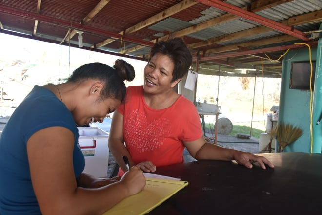 Thia King, 19, left, a Tinian mayor's office staff, takes notes as she visits May Valiente, 50, on Nov. 3, 2018. The mayor's office staff were having residents fill out paperwork for aid after Super Typhoon Yutu, which struck the island on Oct. 24 and 25.