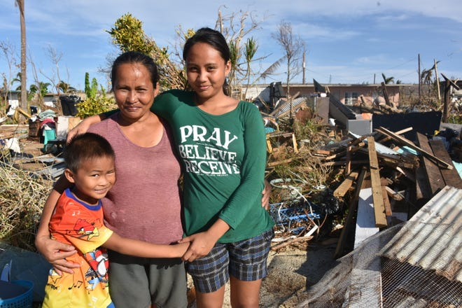 Josie Balagtas, 46, and her children Rose Lynn, 18, and Jaber, 8, are shown in front of their destroyed home on Nov. 3, 2018, on Tinian. The family stayed with friends in a concrete house to ride out Super Typhoon Yutu, which struck the island on Oct. 24 and 25. They were unharmed, but their house was flattened.