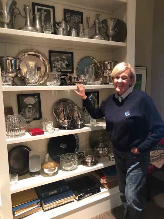 Founder of Anchorsaway Ministry and Indiana Hall of Fame golfer, Nancy Fitzgerald, stands in front of one of her trophy cases.