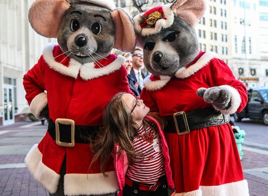 Children's faces light up as holiday characters greet them with warm hugs outside the Hilbert Circle Theatre, before the IPL Yuletide Celebration, Indianapolis, Wednesday, Dec. 20, 2017. Center, Shelby Stevens, 6, looks up at two Christmas mice.