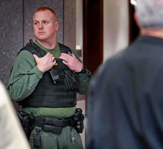 Sheriff's deputy watches as people  wait in line to enter the Hamilton Superior Court No, 1 for the disposition hearing for the suspect in the Noblesville West Middle School shooting, at the Hamilton County Courthouse, Monday, Nov. 5, 2018.