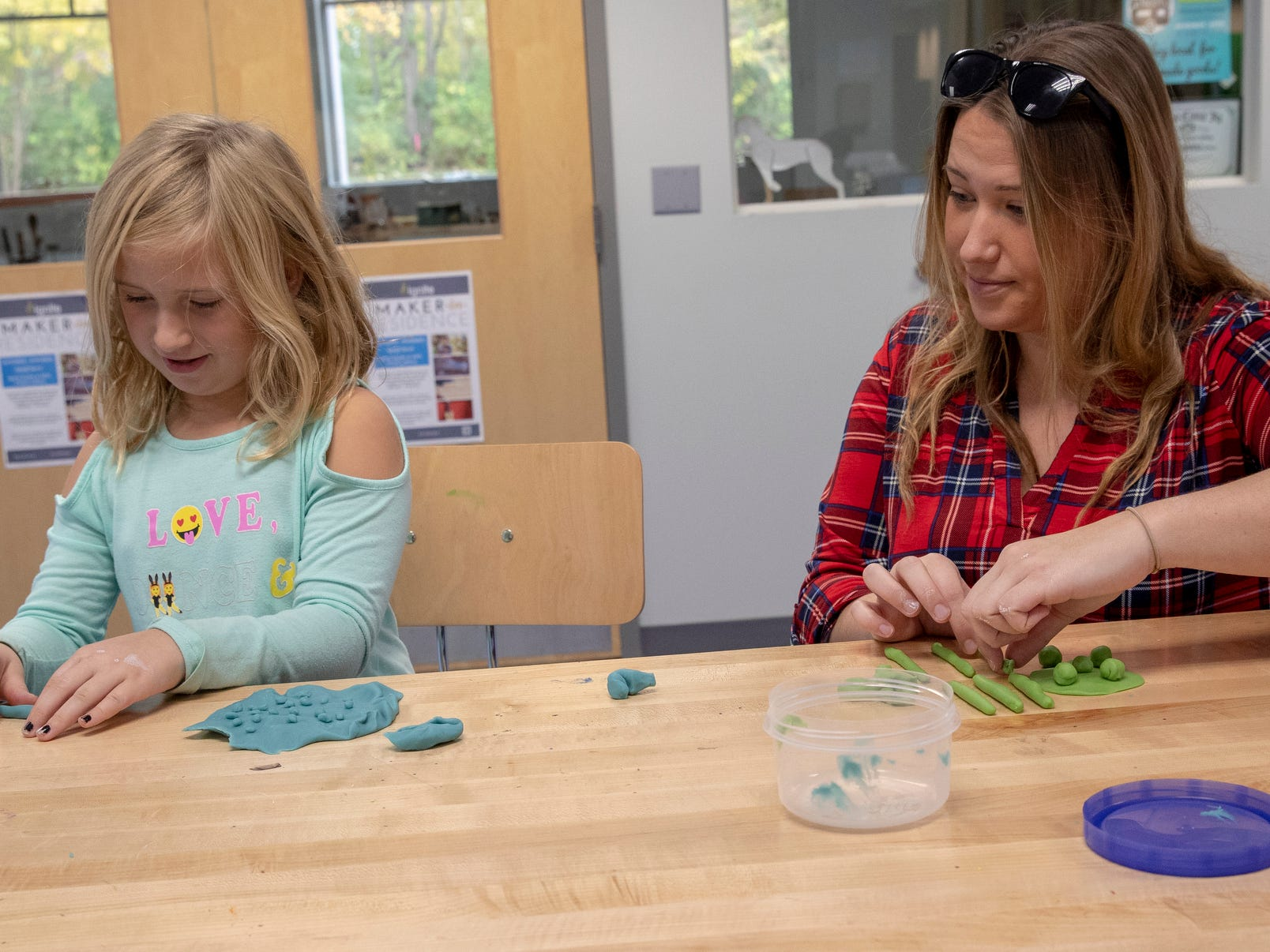 Annalise Baker, 6, Fishers, works with some playdough with her mother Lisa Schuiteboer at Ignite, a new shared work space for artists and creative people at Hamilton East Public Library in Fishers, Sunday, Nov. 4, 2018. The facility is open during regular open hours and has spaces for pottery, videography, 3D printing, and a host of other activities.