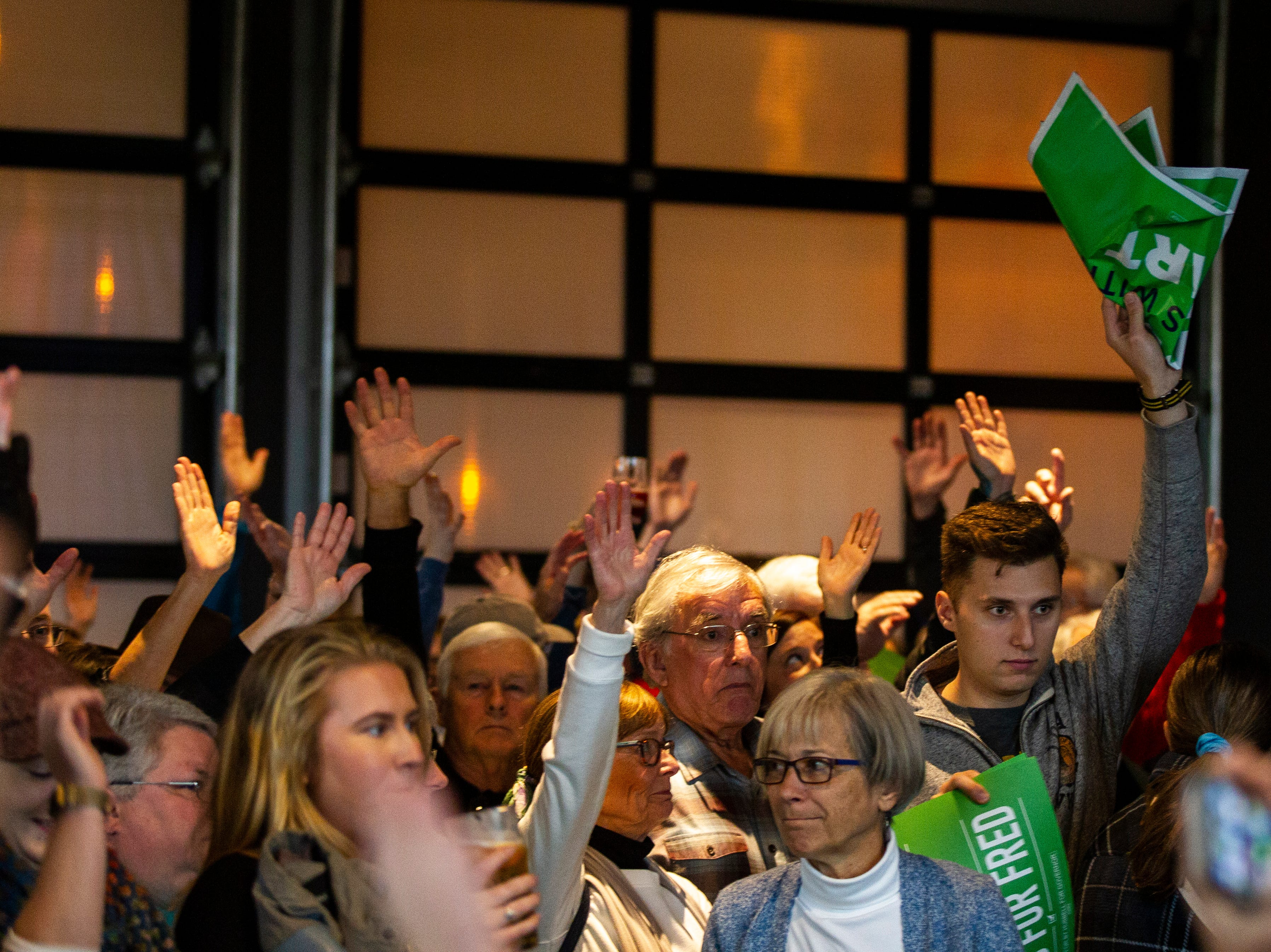 Hubbell supporters raise their hands signifying that they had already voted before a rally on Sunday, Nov. 4, 2018, at Big Grove Brewery in Iowa City.
