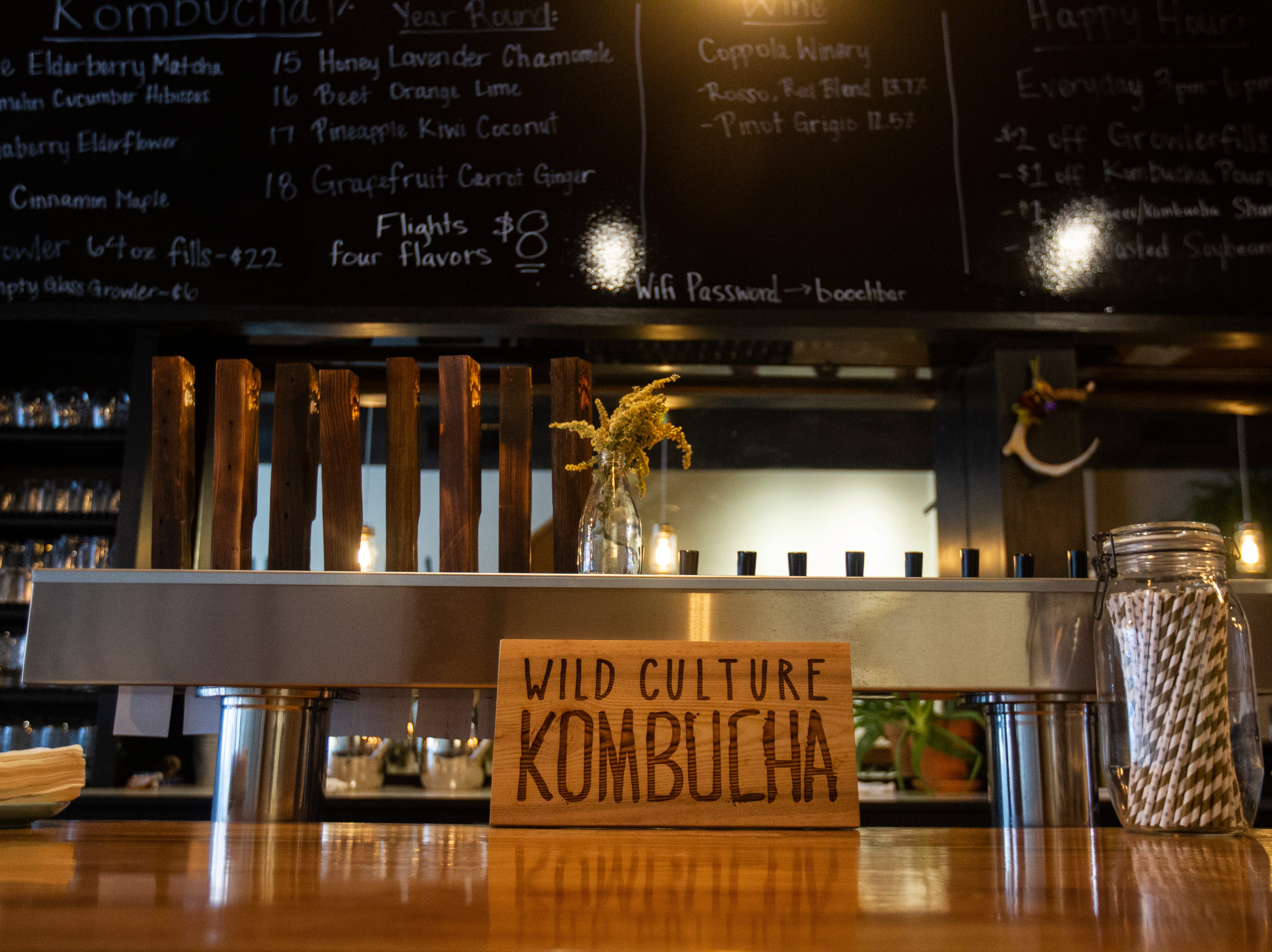 A sign rests on the bar in front of kombucha taps on Wednesday, Oct. 31, 2018, inside Wild Culture Kombucha in Iowa City.