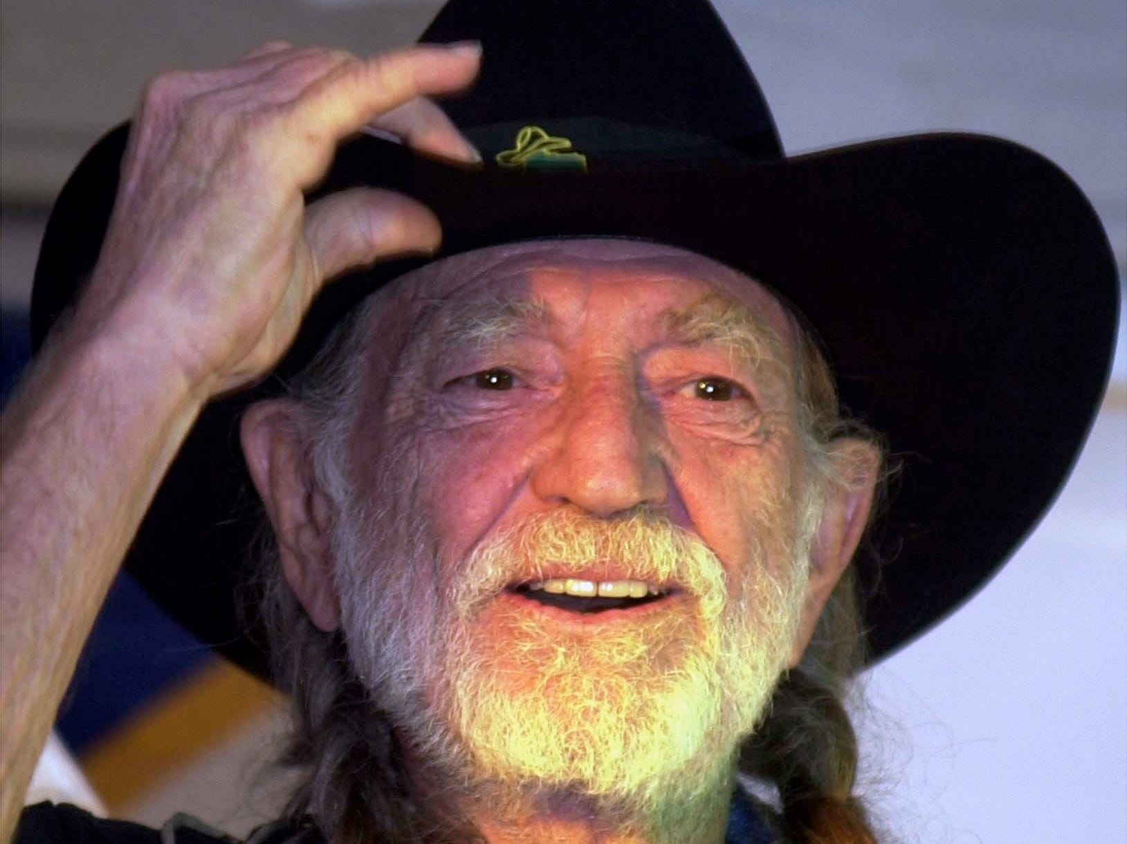 "Country legend Willie Nelson greets the crowd while taking the stage Tuesday evening, Dec. 30, 2003, at Texas Roadhouse in Owensboro, Ky. Nelson made a surprise visit for a Willie-Oke contest and sang ""On The Road Again"" with the winner. He will be performing on Wednesday evening in Nashville, Tenn."