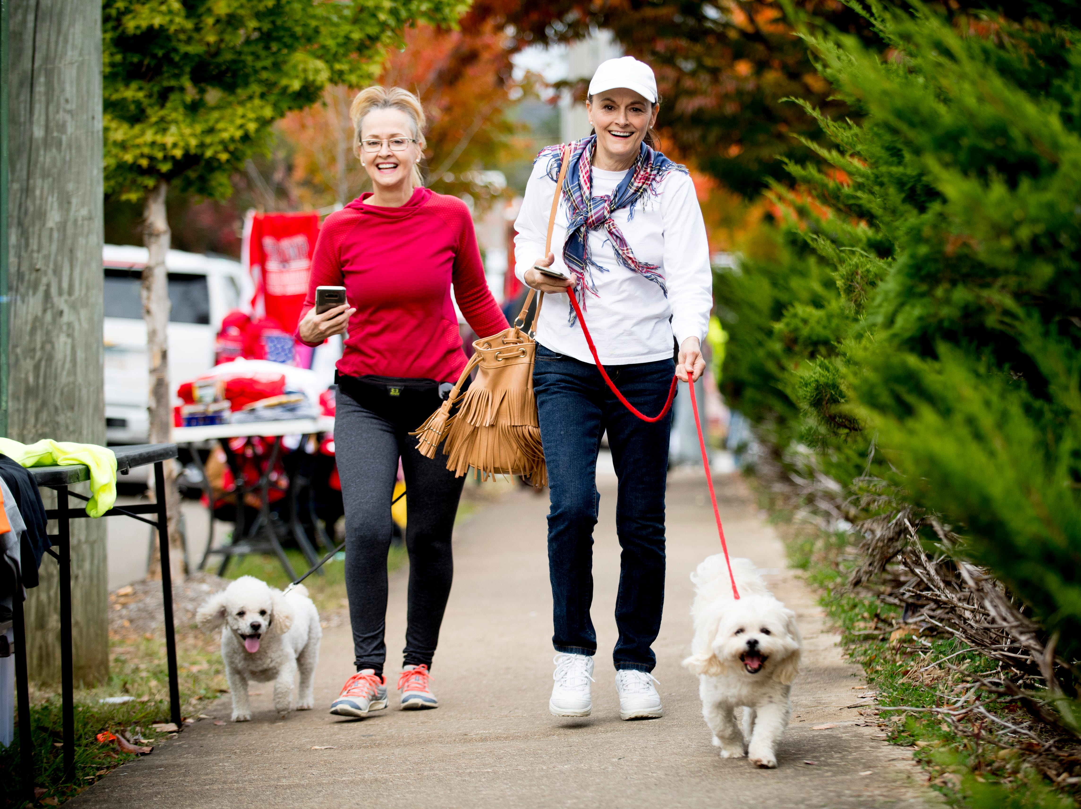 """Lisa Roberts, right, and Christi Roberts walk their pups Hugo and Joey, both poodle mixes, ahead of President Donald J. Trump's """"Make America Great Again"""" Rally at McKenzie Arena in Chattanooga, Tennessee on Sunday, November 4, 2018."""