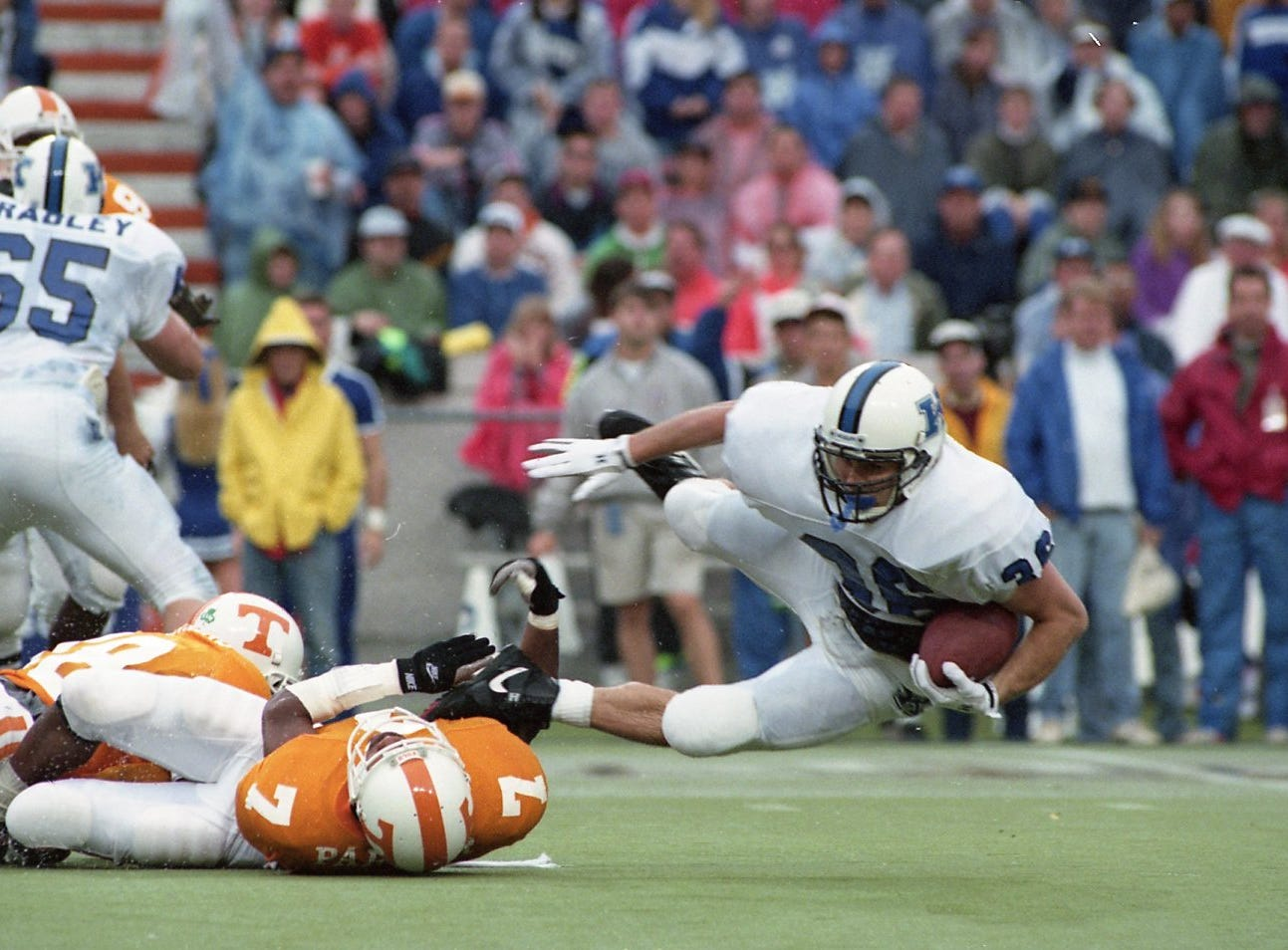 Kentucky's Matt Riazzi tumbles after being tackled by Tennessee's DeRon Jenkins and Jason Parker Saturday, Nov. 21, 1992.
