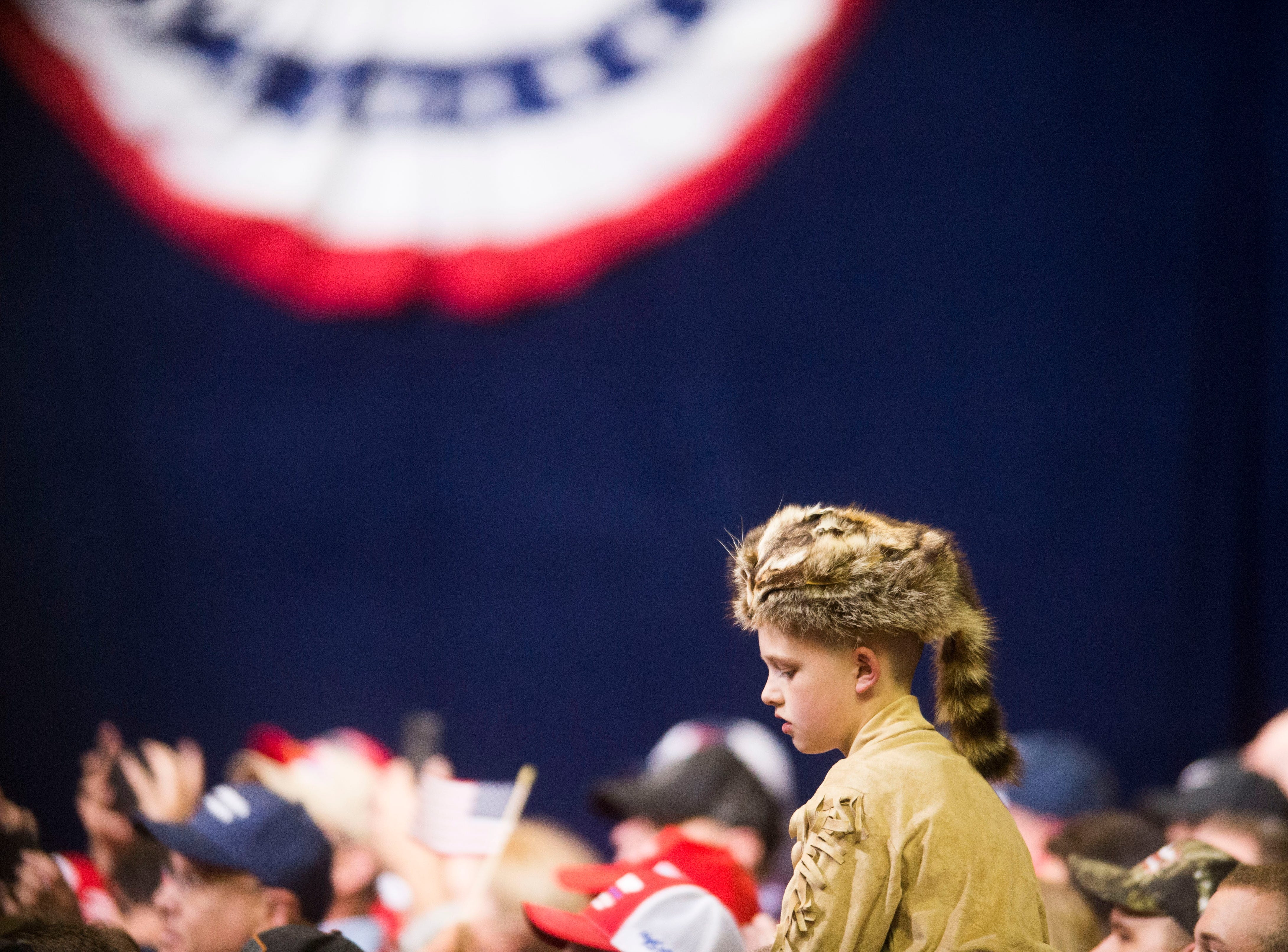 A young Donald Trump supporter listens during a Donald Trump rally in support of U.S. Rep. Marsha Blackburn for the U.S. Senate at McKenzie Arena in Chattanooga, Sunday, Nov. 4, 2018.