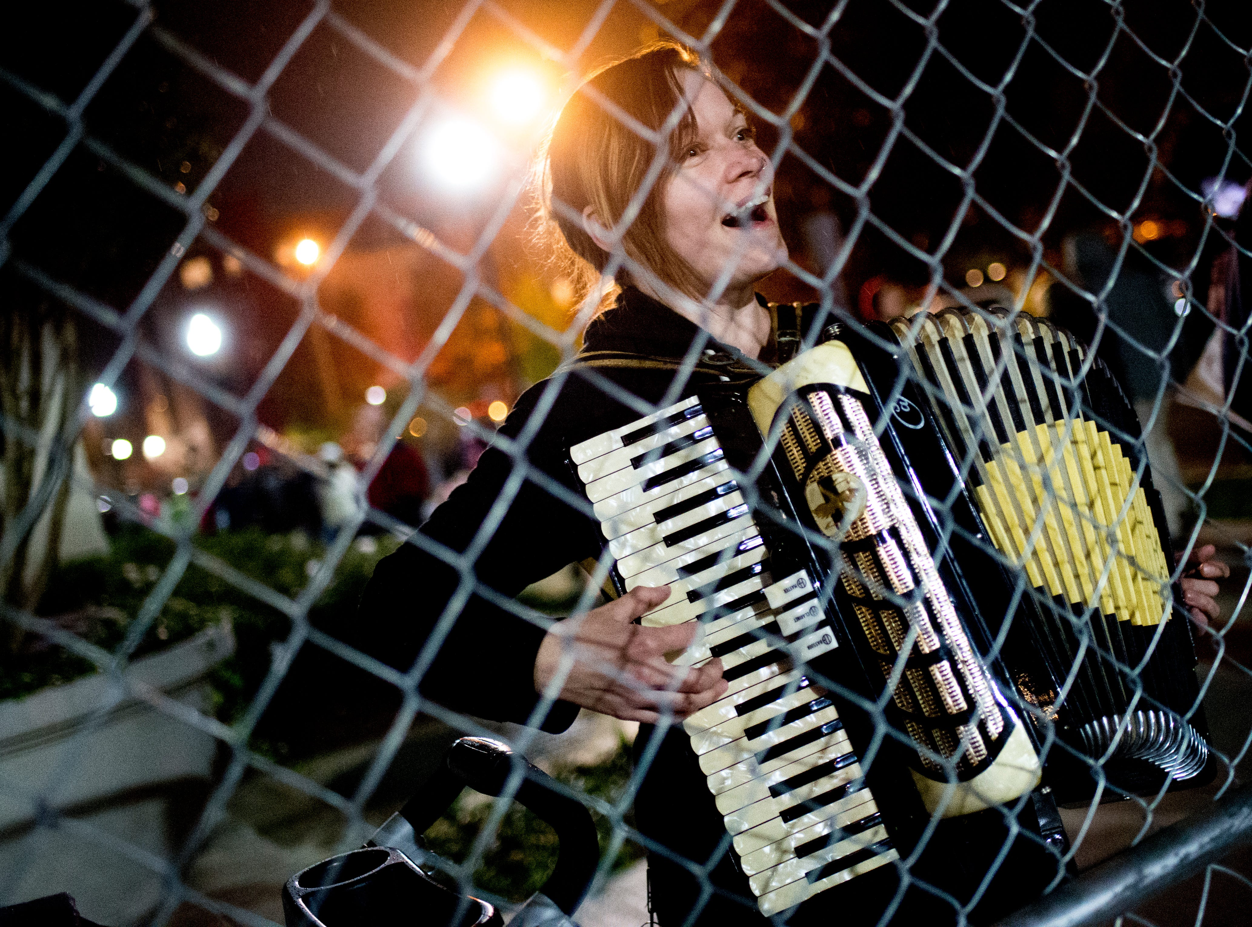 """Amanda Cagle, of Chattanooga, sings in protest with her accordion during President Donald J. Trump's """"Make America Great Again"""" Rally at McKenzie Arena in Chattanooga, Tennessee on Sunday, November 4, 2018."""