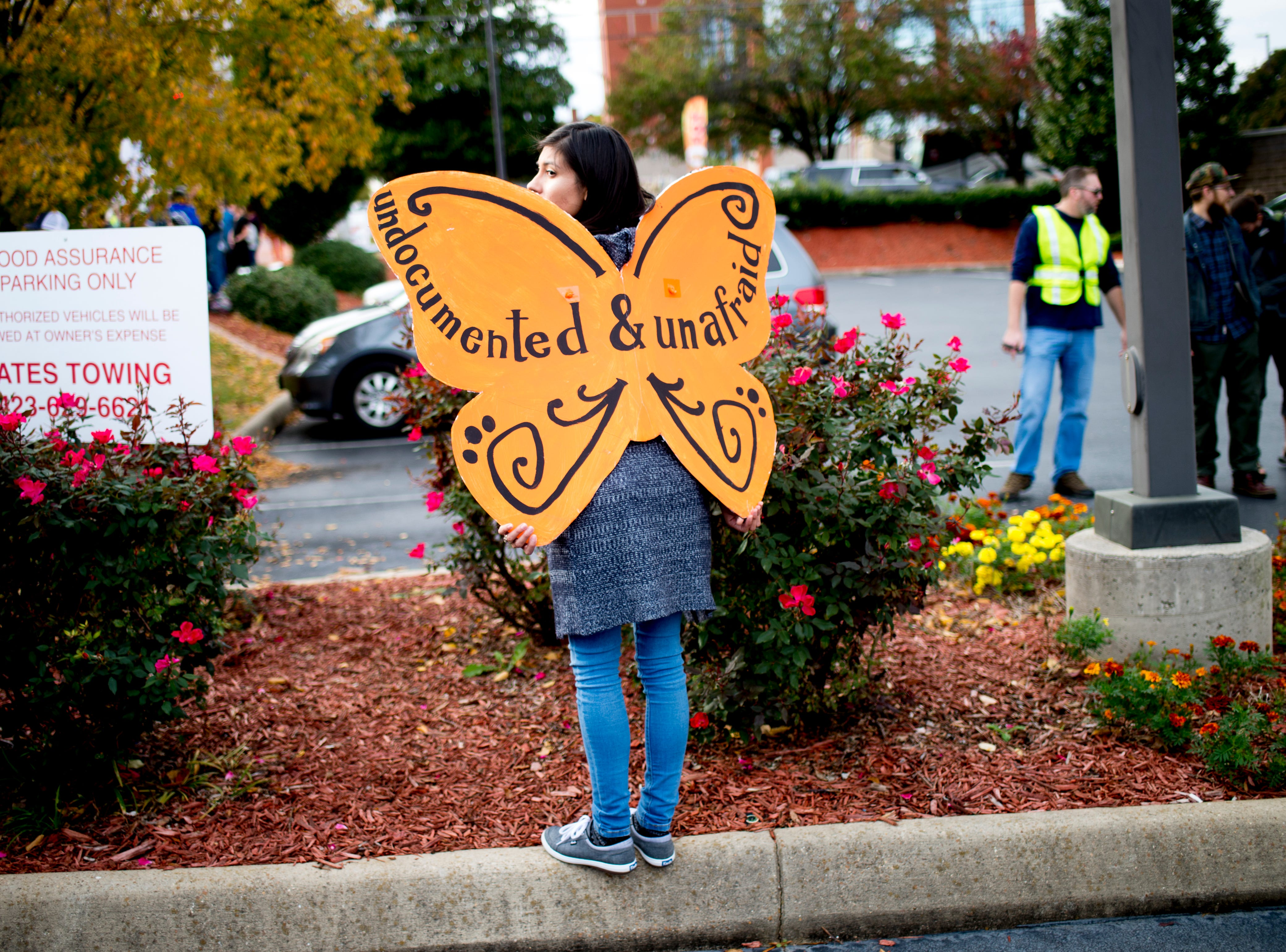 """A protestor wears butterfly wings reading """"Undocumented & Unafraid"""" ahead of President Donald J. Trump's """"Make America Great Again"""" Rally at McKenzie Arena in Chattanooga, Tennessee on Sunday, November 4, 2018."""